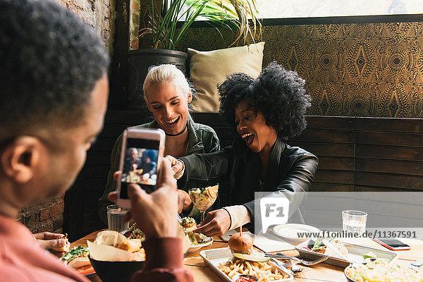 Mann fotografiert Freunde im Restaurant
