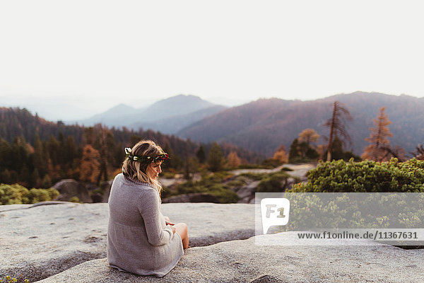 Rear view of woman sitting on rocks in mountains,  Sequoia national park,  California,  USA