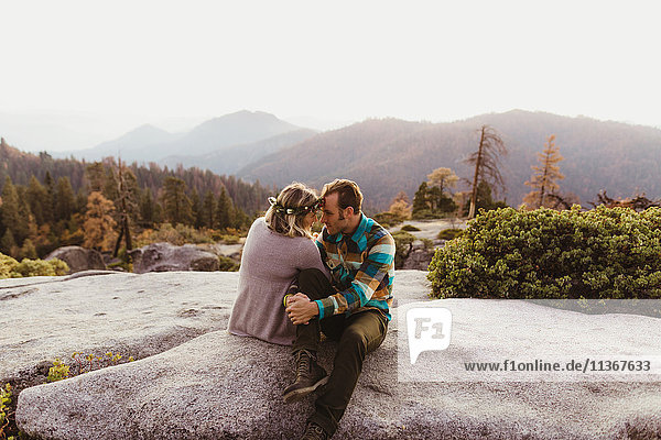 Couple sitting on rocks in mountains  Sequoia national park  California  USA