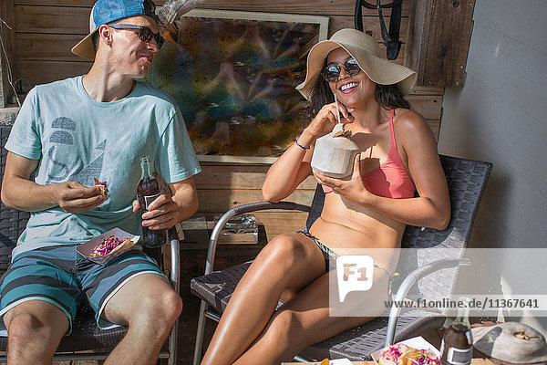 Junges Paar beim Sonnenbaden und Entspannen auf der Veranda von Rockaway Beach  New York State  USA