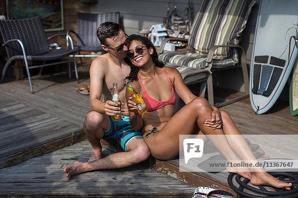 Junges Paar in Bikini und Badeshorts mit Bierflaschen auf der Veranda  Rockaway Beach  Bundesstaat New York  USA