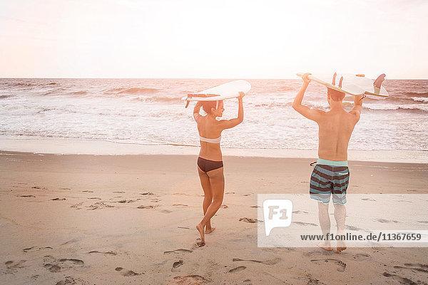 Rückansicht eines jungen Paares mit Surfbrettern auf dem Kopf am Rockaway Beach  New York State  USA