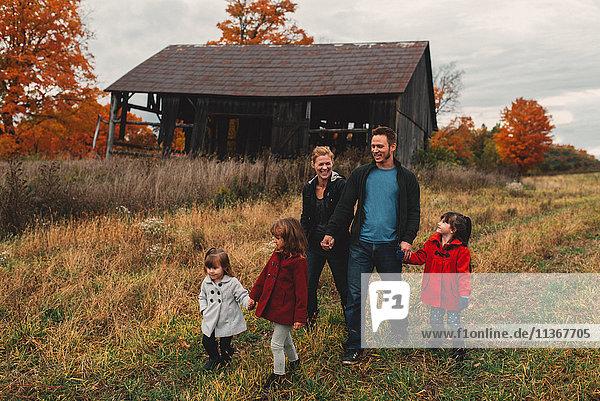 Mittlere erwachsene Familie mit drei Töchtern  die Händchen halten und auf dem Feld spazieren gehen