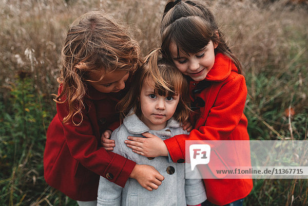 Portrait of two girls hugging toddler sister in field