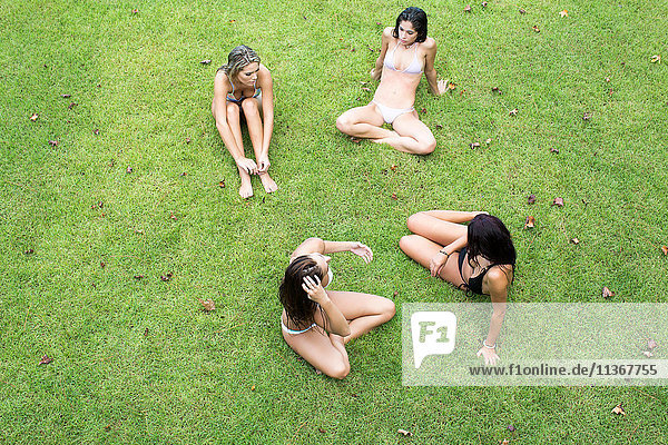 Overhead view of four women in bikinis sitting on lawn  Santa Rosa Beach  Florida  USA