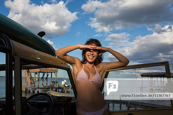 Portrait of young woman in bikini shielding eyes on pier  Santa Rosa Beach  Florida  USA