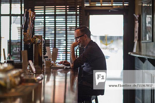 Barkeeper tippt mit Laptop am Tresen einer Gaststätte