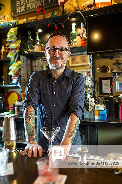 Porträt eines Barkeepers mit Cocktailglas am Tresen einer Gaststätte