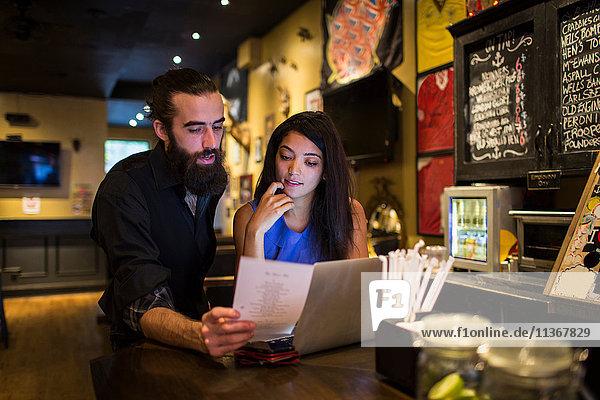 Junges Paar liest Speisekarte am Stammtisch