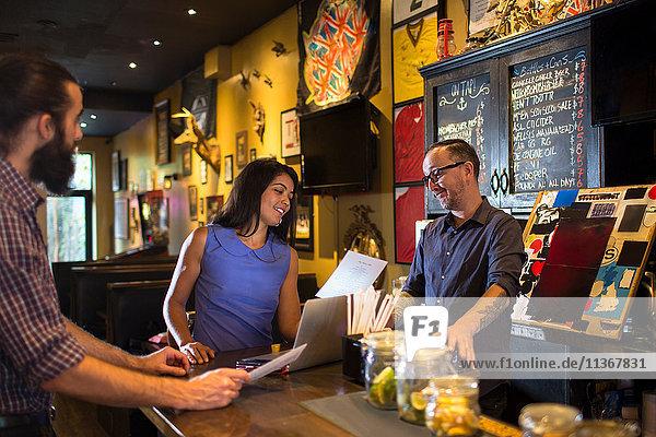 Barkeeper liest Speisekarte mit jungem Ehepaar am Tresen