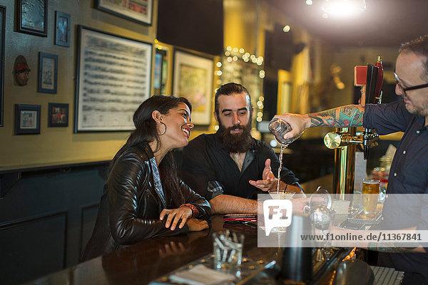 Barkeeper schenkt Cocktail für junges Paar in einer Gaststätte ein