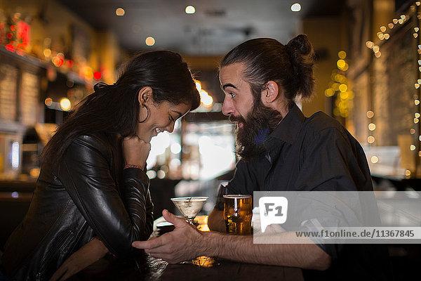 Junges Paar unterhält sich am Tisch bei Cocktail und Bier in einer Gaststätte