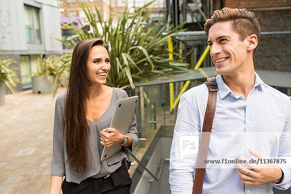 Junge Geschäftsfrau und Mann beim Gehen und Sprechen  London  UK