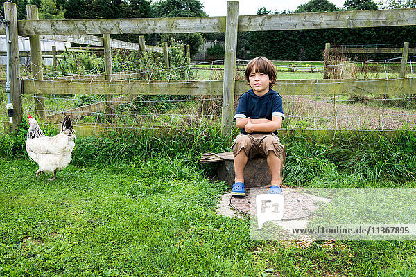Boy sitting on farm with chicken