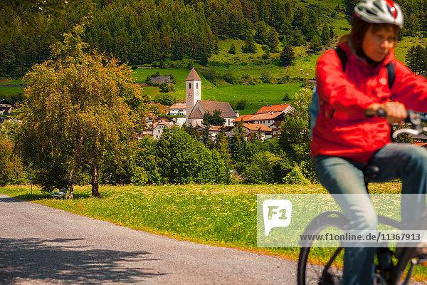 Ältere Frau radelt entlang des Dorfwegs im Vinschgau  Südtirol  Italien