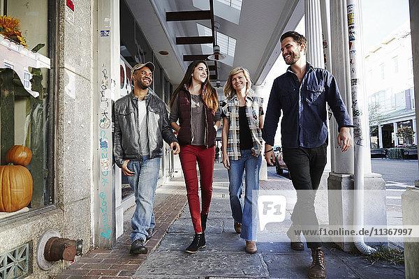 Zwei junge Männer und zwei junge Frauen gehen lächelnd einen Bürgersteig entlang.