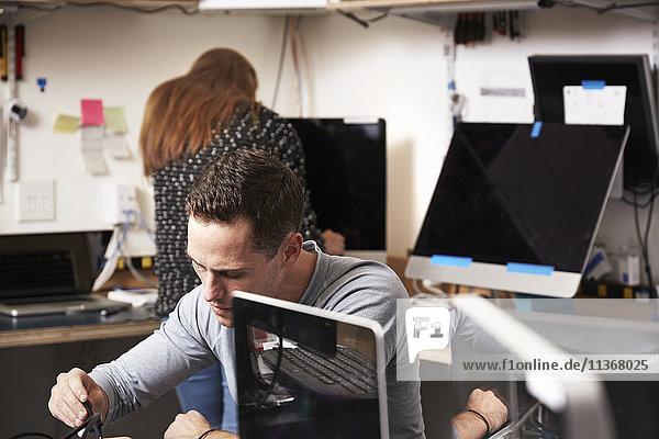 Ein junger Mann und eine junge Frau  die in einem Technologielabor oder einer Reparaturwerkstatt an Computern arbeiten.