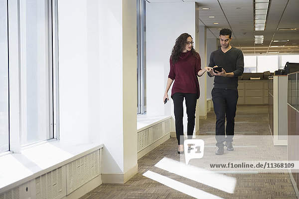 Young people walking side by side in corridor with digital tablet
