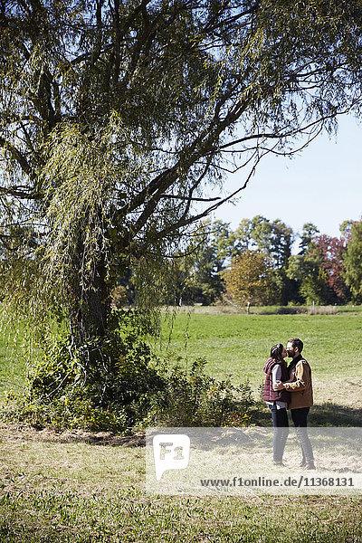 Eine junge Frau und ein junger Mann stehen neben einem Baum auf einem Feld und küssen sich.