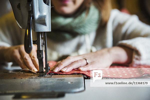 Werkstatt für Polsterei. Eine sitzende Frau arbeitet mit einer Industrienähmaschine und näht Stoff. Werkstatt für Polsterei. Eine sitzende Frau arbeitet mit einer Industrienähmaschine und näht Stoff.