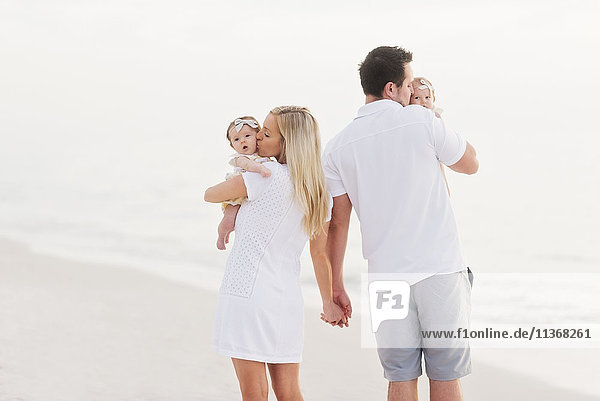 Parents walking with babies (2-5 months) along seashore