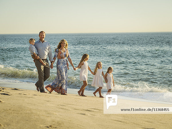 Family with children (12-17 months  4-5  6-7  8-9) walking on beach with sea in background