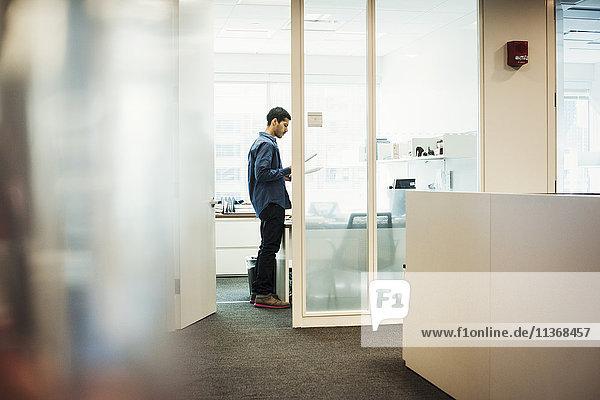 Ein Mann  der in einem Büro steht und auf Zettel schaut.