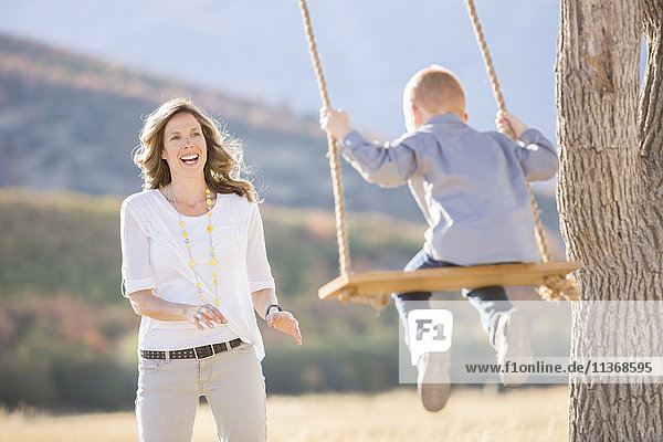 Mother with child (4-5) sitting on swing