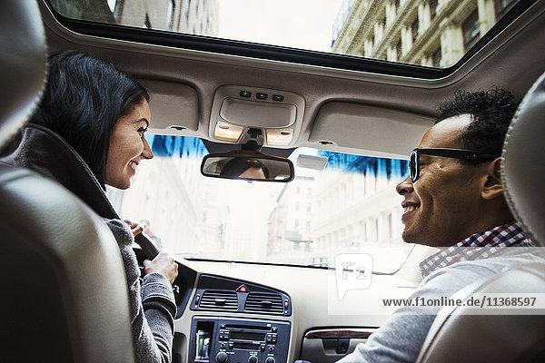 Eine junge Frau und ein junger Mann in einem Auto  die sich vom Rücksitz aus gesehen lächelnd ansehen.