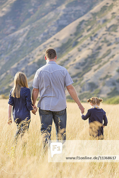 Father with two daughters (4-5  8-9) walking in field