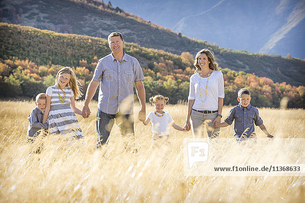 USA  Utah  Provo  Family with three children (4-5  6-7  8-9) standing in field