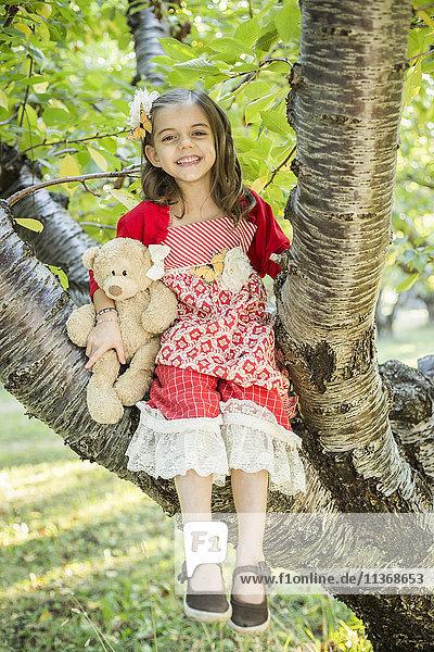 Girl with teddy bear sitting on tree