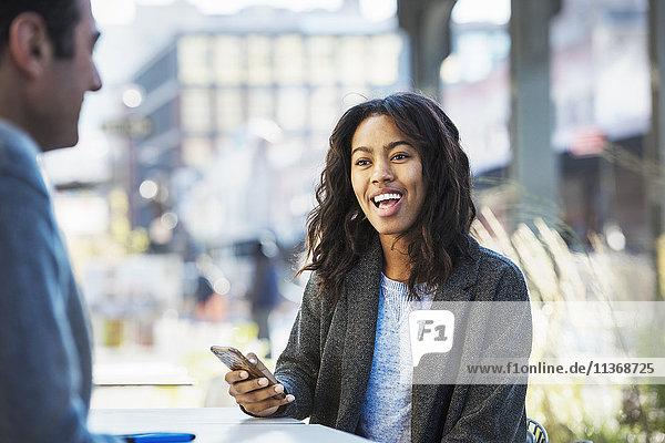 Eine Frau hält ein Mobiltelefon in der Hand und spricht mit einem Mann auf einer Straße in der Stadt.