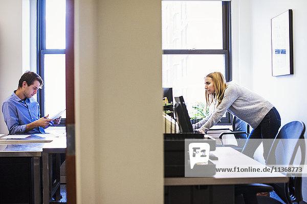 Die Aufnahme eines jungen Mannes,  der in einem Büro sitzt und auf ein Mobiltelefon schaut,  und einer jungen Frau,  die in einem anderen Büro steht und an einem Computer arbeitet.