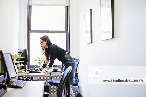 A young woman standing at a desk looking at a computer screen.