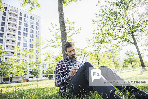 Young man sitting in a park and writing in notepad