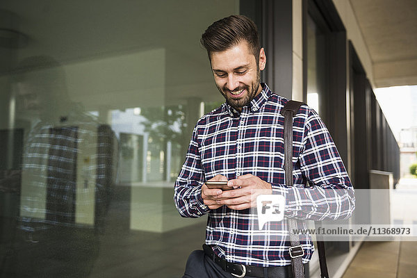 Young man text messaging on mobile phone and smiling