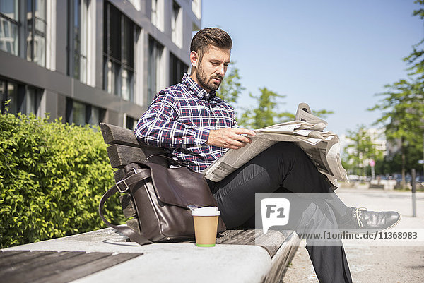 Young man sitting on bench and reading newspaper