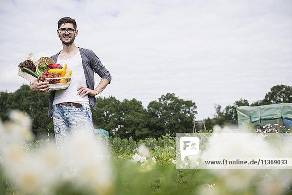 Mid adult man harvesting vegetables from community garden