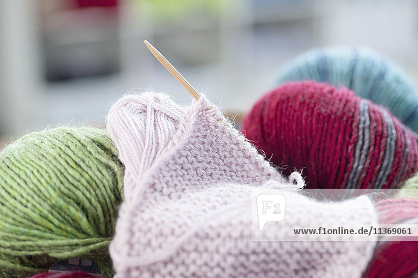 Balls of wool with knitting needle in salesroom Balls of wool with knitting needle in salesroom