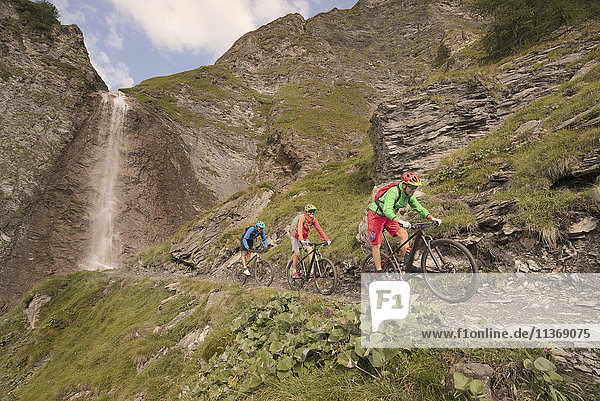 Three mountain bikers riding on hill at waterfall  Zillertal  Tyrol  Austria
