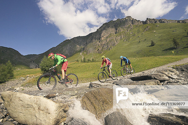 Three mountain bikers crossing stream on mountain  Zillertal  Tyrol  Austria