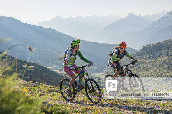 Two mountain biker friends riding on uphill  Zillertal  Tyrol  Austria