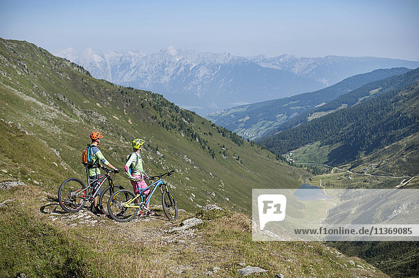Young couple of mountain bikers looking at view in alpine landscape  Zillertal  Tyrol  Austria