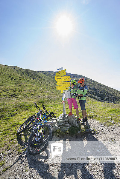 Young couple of mountain bikers certificating their bike tour at sign posts  Zillertal  Tyrol  Austria