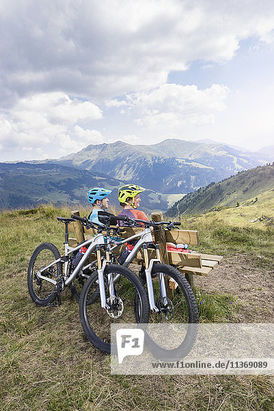 Young couple of mountain bikers sitting on bench in alpine landscape  Zillertal  Tyrol  Austria