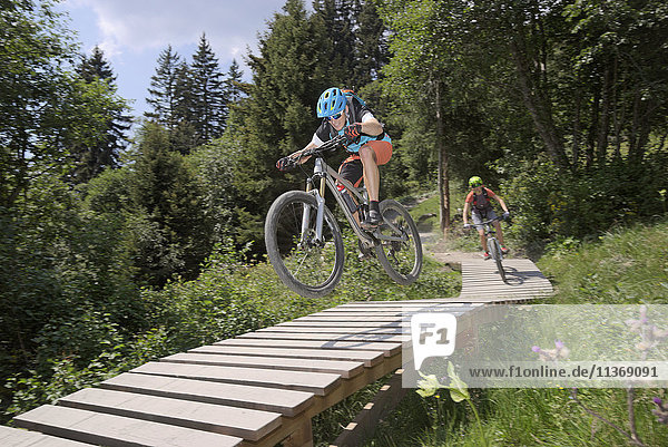 Two mountain bikers riding on footbridge through forest  Zillertal  Tyrol  Austria