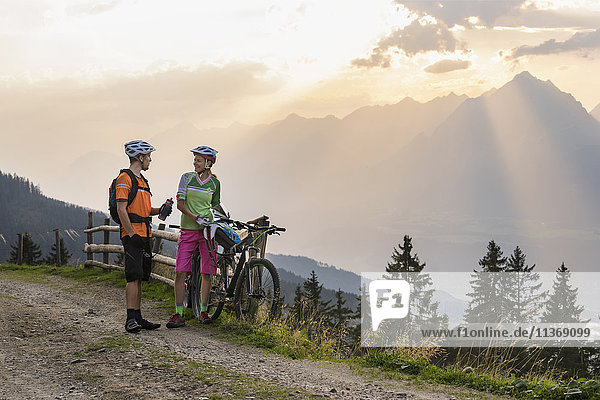 Young couple of mountain bikers standing on dirt road during sunset  Zillertal  Tyrol  Austria