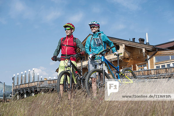 Young couple of mountain bikers standing in alpine landscape and looking at view  Zillertal  Tyrol  Austria