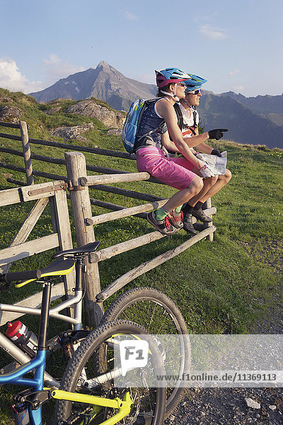Young couple of mountain bikers with map sitting on wooden fence  Zillertal  Tyrol  Austria